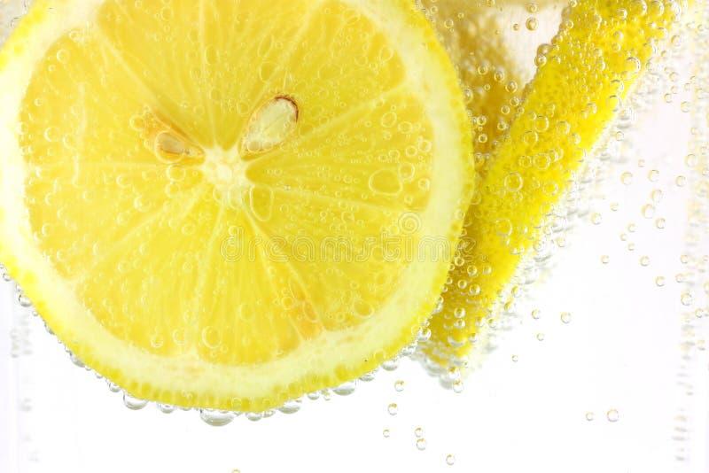 Zitronescheiben im Wasser lizenzfreie stockfotos