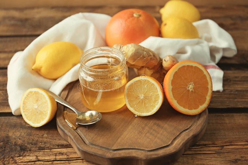 Zitrusfrüchte, Ingwer und Glas mit Honig lizenzfreie stockbilder