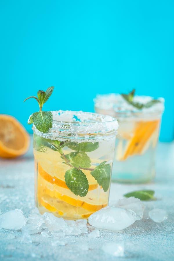 Zitrusfruchtlimonadenwasser mit Zitrone geschnittenem gesundem und Detoxwassergetränk im Sommer auf Holztisch mit Blau erleichter stockbild