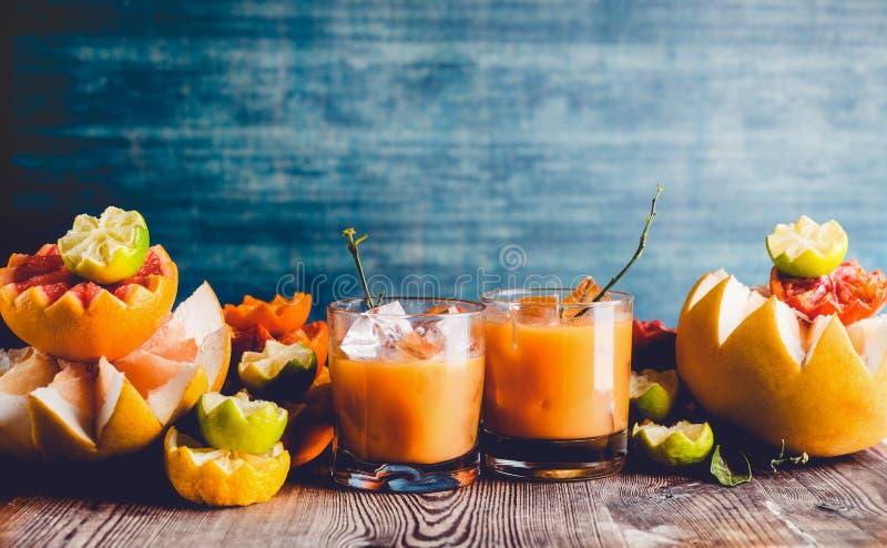 Zitrusfruchtsaftmischung in den Gl?sern auf Tabelle mit verschiedenen Zitrusfruchtbestandteilen: Kalk, Pampelmuse, Orange, Tanger lizenzfreie stockfotografie