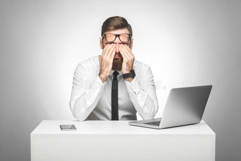 Zitten de gek vermoeide jonge manager in wit overhemd en de avondkleding in bureau die ogen na het lange werk aangaande de comput royalty-vrije stock foto