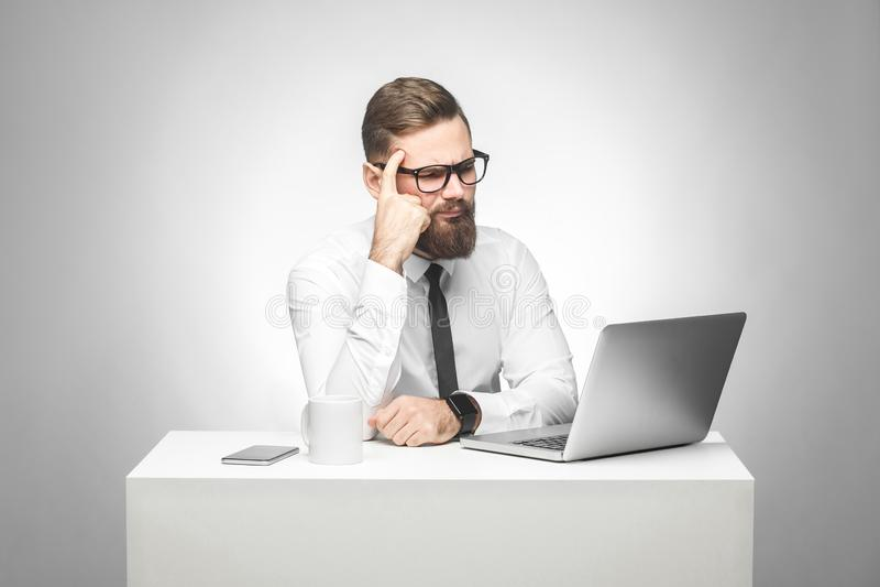 Zitten de Thoughful gebaarde jonge werkgever in wit overhemd en de avondkleding in bureau op bureau en het letten op dagelijks ra stock fotografie