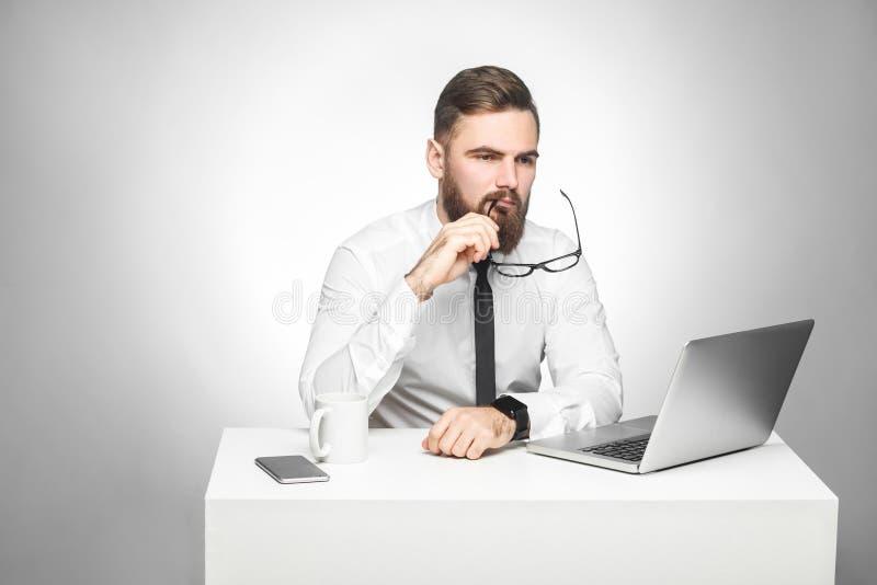 Zitten de Thoughful gebaarde jonge werkgever in wit overhemd en de avondkleding in bureau op bureau en het letten op dagelijks ra royalty-vrije stock afbeeldingen