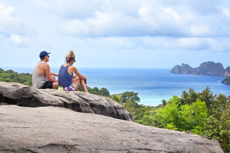 Zitten de de twee mensen jonge man en vrouw hoog bovenop berg, blauwe overzees, hemel met wolken en groene bomen mooie mening stock foto's
