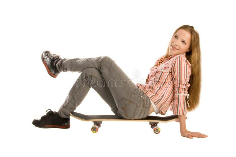 Zittend op skateboard, dat omhoog eruit ziet stock foto's