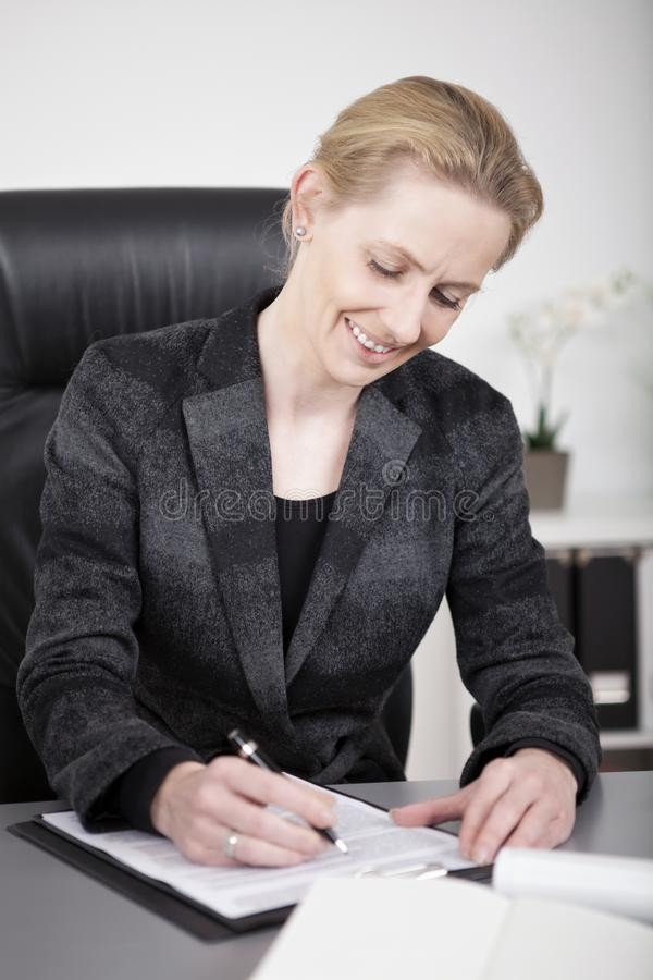 Zittende Gelukkige Onderneemster Writing bij haar Bureau stock foto's