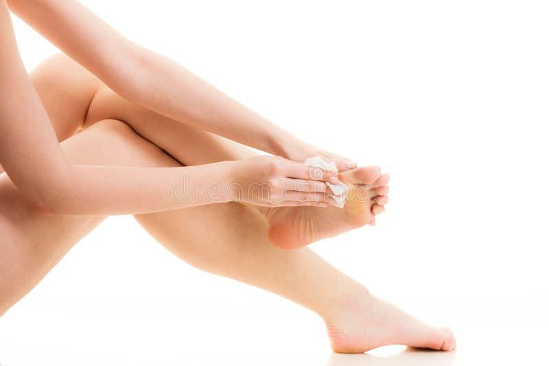 Zittende naakte vrouw die haar voeten schoonmaken royalty-vrije stock afbeeldingen