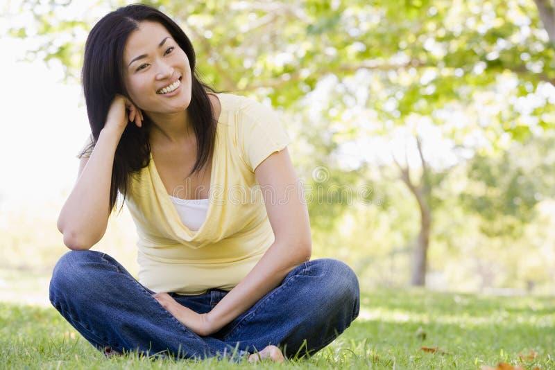 Zitting die van de vrouw de in openlucht glimlacht stock foto