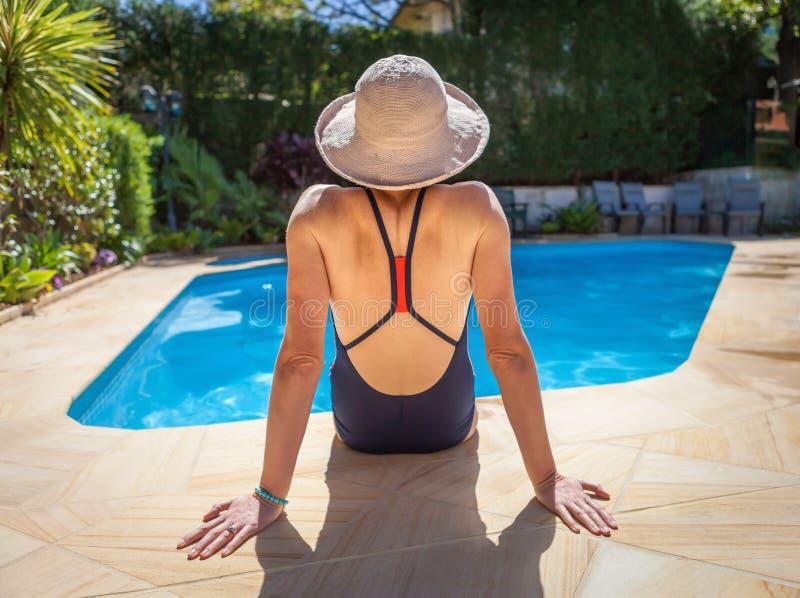 Zitting o de rand van een pool die in de zomer een hoed dragen stock foto's