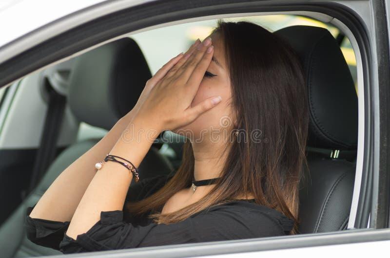 Zitting van de close-up frustreerde de jonge vrouw in auto verstoord op elkaar inwerken, behandelend gezicht in handen, zoals gez stock foto