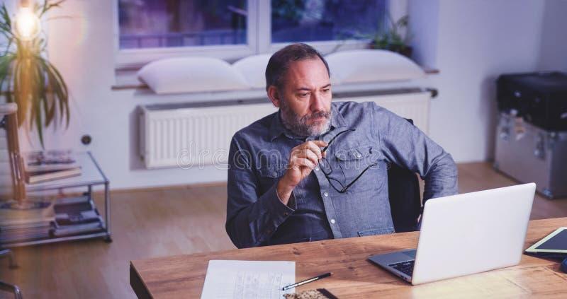 Zitting van de de mensen creatieve directeur van Grey Bearded de rijpe in moderne offi stock foto