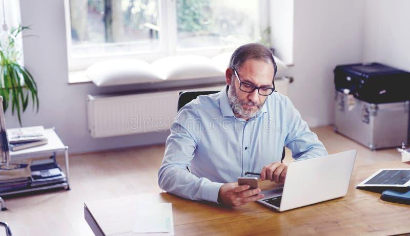 Zitting van de de mensen creatieve directeur van Grey Bearded de rijpe in moderne offi royalty-vrije stock foto