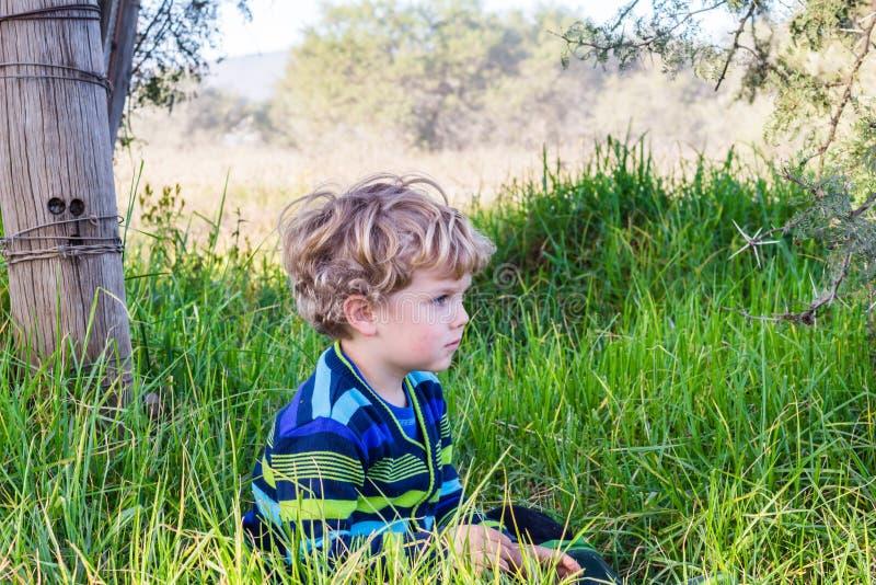 Zitting van de drie éénjarigen de peinzende jongen in het lange gras stock afbeelding