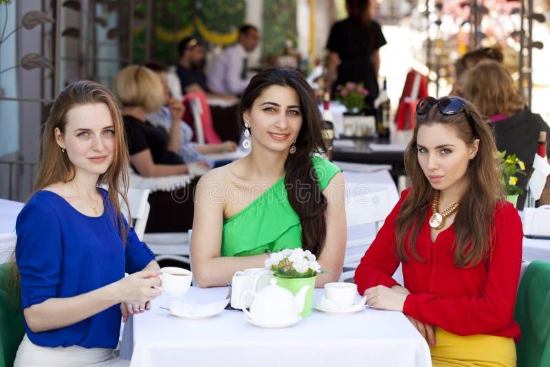 Zitting van de drie de gelukkige meisjesvrouw bij een lijst in de zomer c royalty-vrije stock foto's