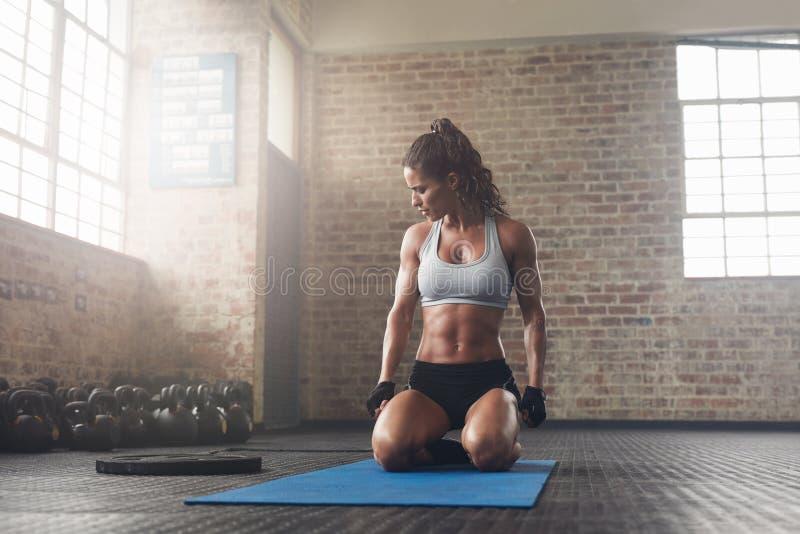 Zitting van de geschiktheids de jonge vrouw op yogamat bij gymnastiek royalty-vrije stock foto
