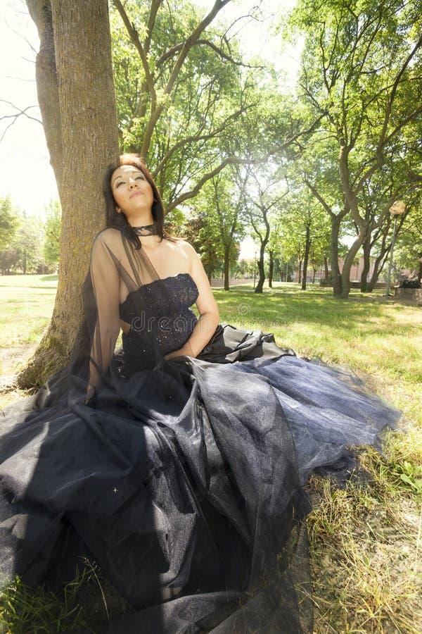 Zitting van de het donkerbruine huwelijks de blauwe kleding van de bruidvrouw dichtbij boom stock foto's