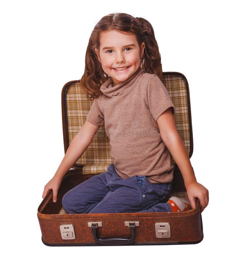 Zitting van de meisjes de donkerbruine baby in een koffer voor geïsoleerde reis royalty-vrije stock afbeelding