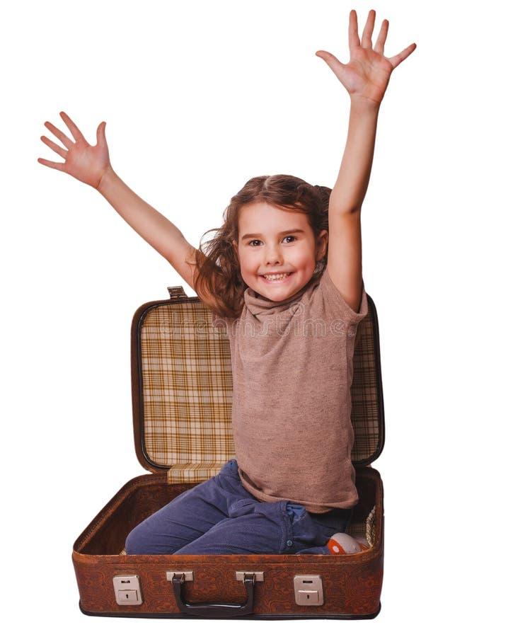Zitting van de meisjes de donkerbruine die baby in koffer voor reis op wh wordt geïsoleerd stock foto