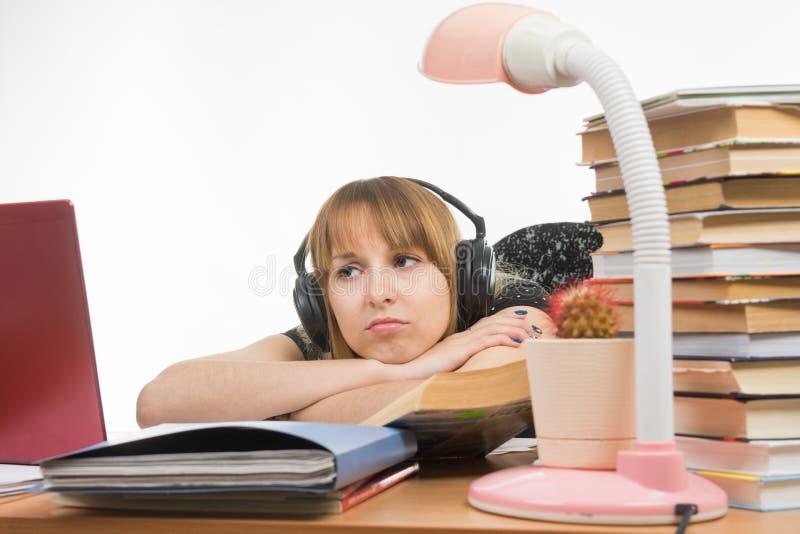 Zitting van de meisjes de droevige student bij lijst die hoofdtelefoons dragen en aan muziek luisteren royalty-vrije stock afbeeldingen