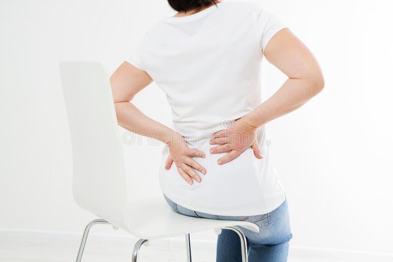 Zitting van de midden-leeftijds lijdt de donkerbruine vrouw op stoel aan rugpijn, geneeskunde royalty-vrije stock afbeelding
