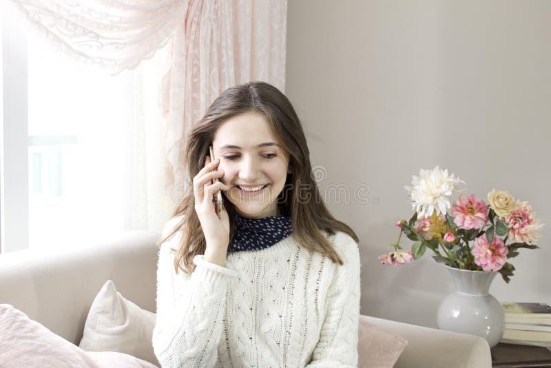Zitting van de Oung de gelukkige vrouw op de bank thuis terwijl het spreken op telefoon royalty-vrije stock fotografie