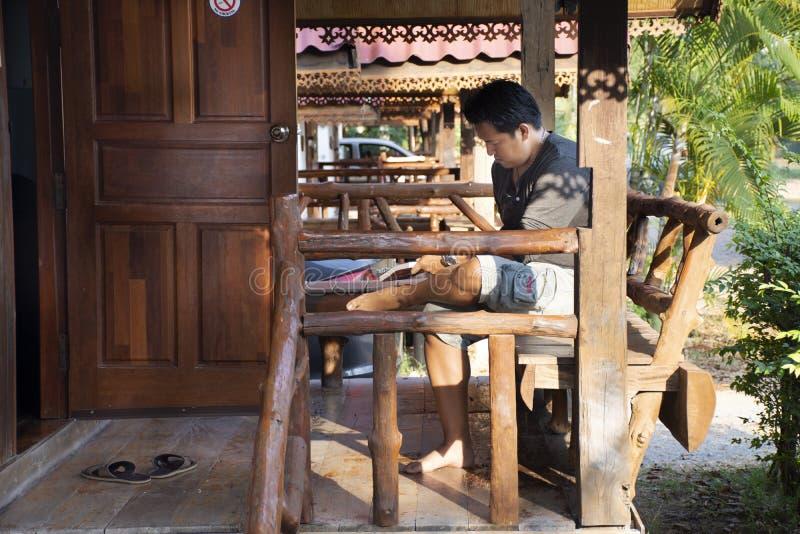 Zitting van de reizigers ontspande de Thaise mens lezingsboek bij houten hut van toevlucht en homestay na huur en rust in ochtend stock foto's