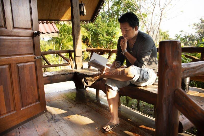Zitting van de reizigers ontspande de Thaise mens lezingsboek bij houten hut van toevlucht en homestay na huur en rust in ochtend stock foto
