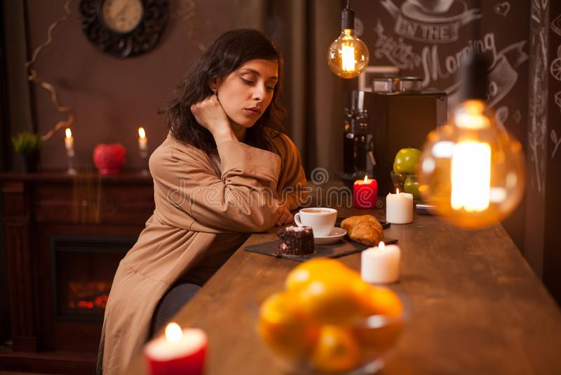 Zitting van de schoonheids winkelen de jonge donkerbruine vrouw bij de bar met een kop van koffie en de smakelijke cake in luxeko royalty-vrije stock foto's