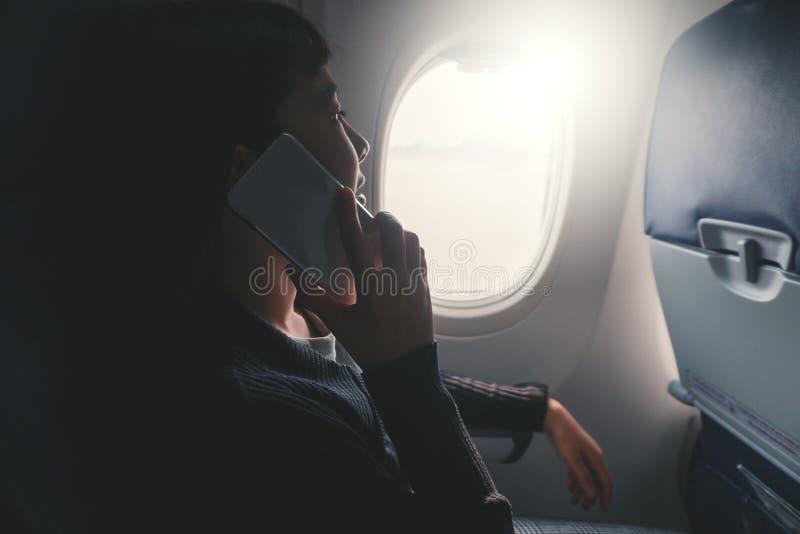Zitting van de toeristen de Aziatische vrouw dichtbij vliegtuigvenster en het gebruiken van Smartphone tijdens vlucht stock afbeelding