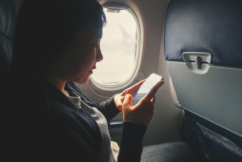 Zitting van de toeristen de Aziatische vrouw dichtbij vliegtuigvenster en het gebruiken van Smartphone tijdens vlucht royalty-vrije stock foto's