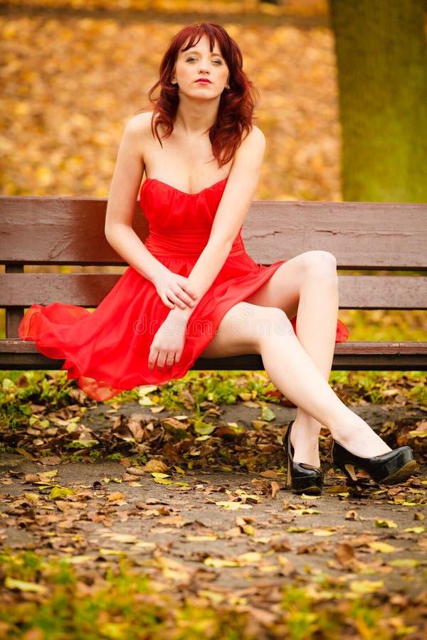 Zitting van de vrouwen de rode kleding op bank in de herfstpark stock fotografie