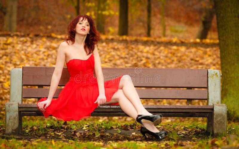Zitting van de vrouwen de rode kleding op bank in de herfstpark royalty-vrije stock afbeeldingen