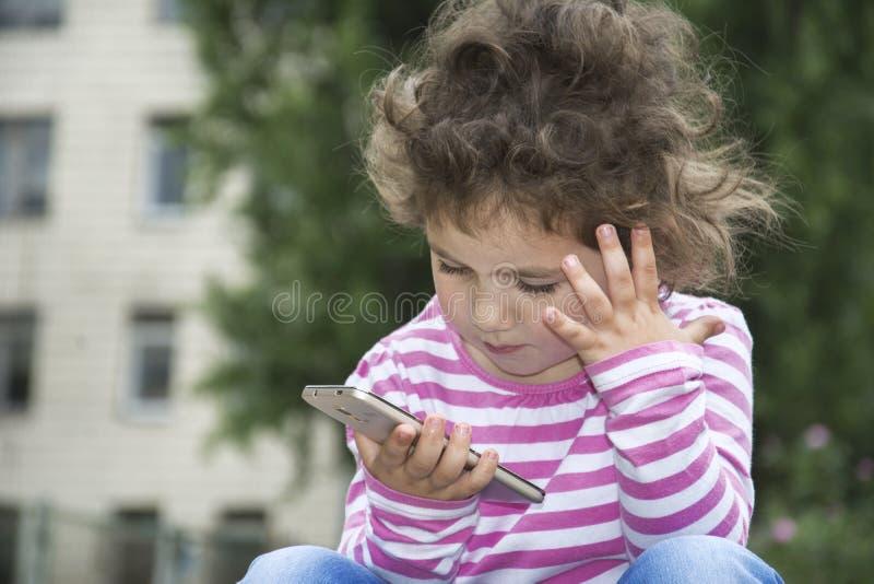 Zitting van het de zomer staren de openlucht krullende meisje en iets bij ph stock foto