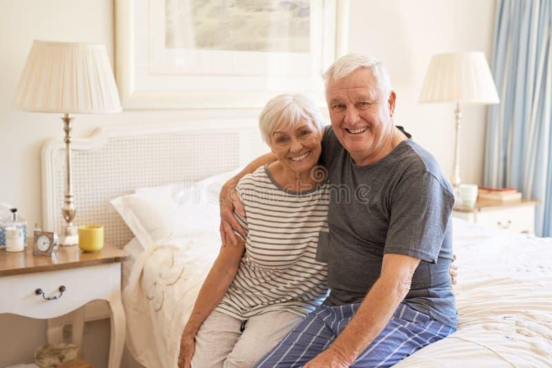 Zitting van het inhouds de hogere paar op hun bed in de ochtend royalty-vrije stock afbeelding