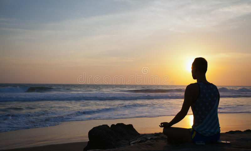 Zittingsmens die yoga op kust van oceaan doen stock fotografie