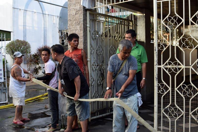 Zivilist erbietet freiwillig sich, Feuerlöschschlauch während des Hausbrandes ziehend, der Innenseemannsliedhäuser ausweidete stockfoto
