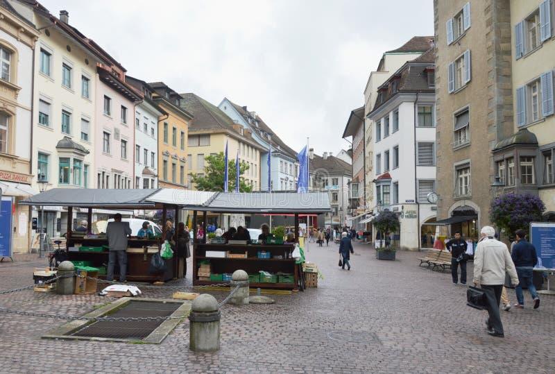 Zivilist und touristischer Kauf irgendein Produkt im Lebensmittelgeschäft auf Straße mittlerer alter Stadt Zürichs lizenzfreie stockfotos