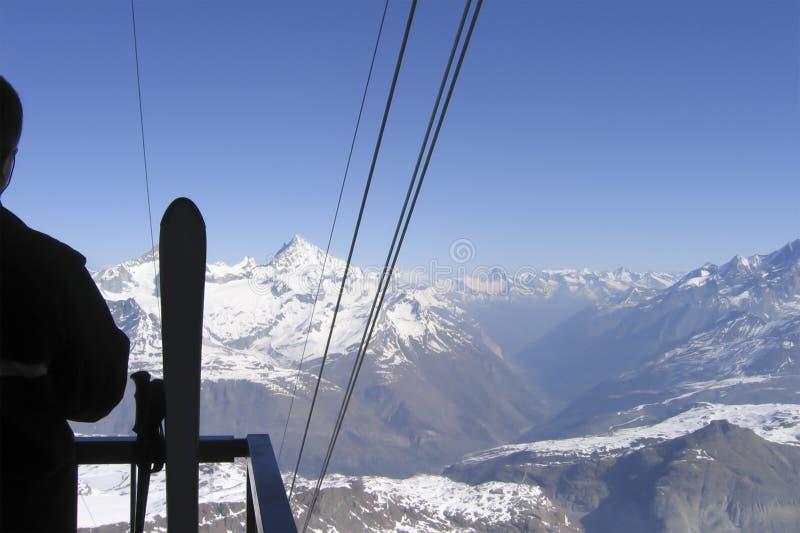 Zjazdowa narciarka patrzeje z góry przy śnieżnym halnym masywem zdjęcie stock