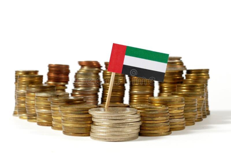 Zjednoczone Emiraty Arabskie flaga z stertą pieniądze monety obraz stock