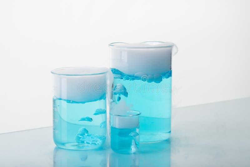 Zlewki z b??kitnym cieczem i suchym lodem na stole Przesublimowanie suchy l?d zdjęcie stock