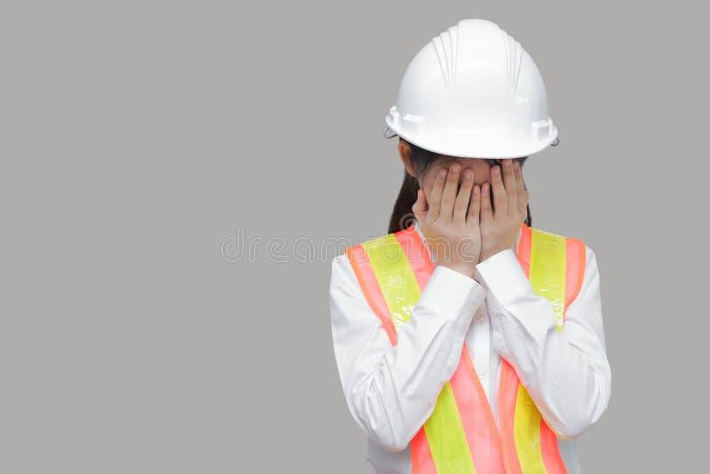 Zmęczona zaakcentowana młoda Azjatycka pracownika nakrycia twarz z rękami na szarość odizolowywał tło obraz royalty free