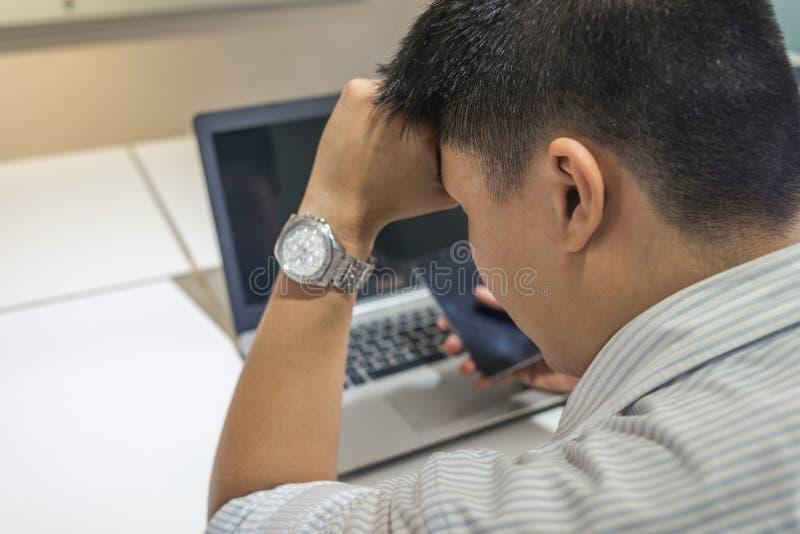 Zmęczony Azjatycki biznesmen z laptopem przy biurem zdjęcie stock