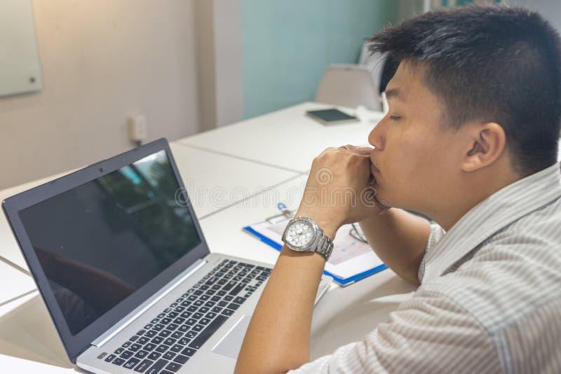 Zmęczony biznesmen z laptopem przy biurem obraz royalty free