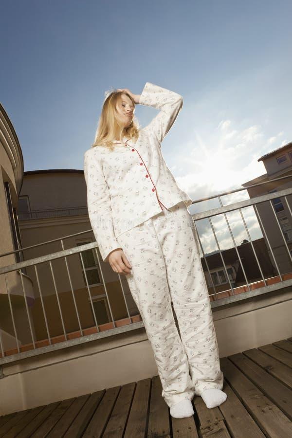 Zmęczeni kobiet stand´s na balkonie zdjęcia royalty free