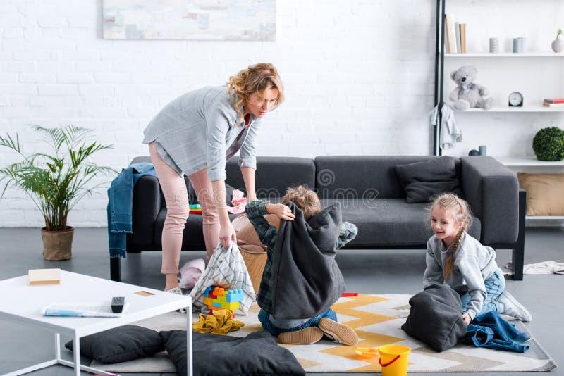 zmęczeni macierzyści patrzeje niegrzeczni dzieciaki walczy z poduszkami ilustracja wektor