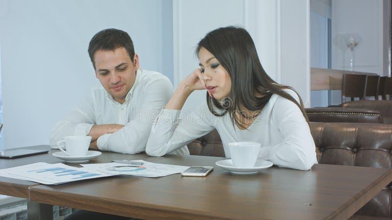 Zmęczeni partnery biznesowi pracuje na projekcie podczas lunchu przy kawiarnią obraz royalty free