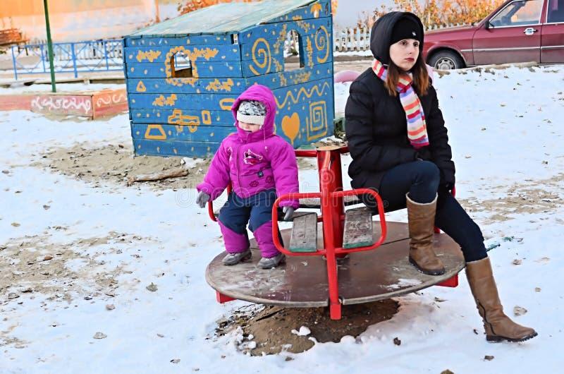 Zmęczeni potomstwa matka i dziecko na huśtawce w zimie zdjęcia stock