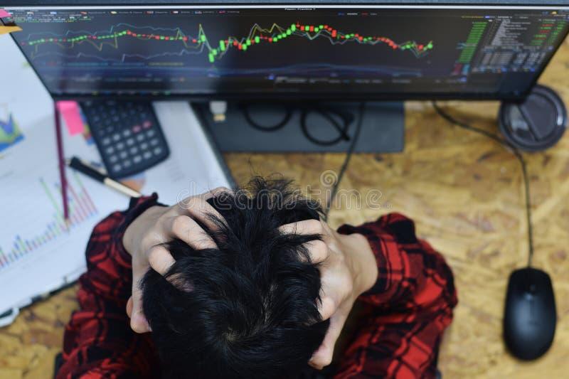 Zmęczenie mężczyzna wręcza trzymać głowę w domu i mieć migreny biuro przez stresu wewnątrz podczas gdy handlujący rynek walutoweg fotografia stock