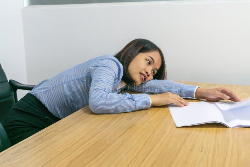 Zmęczona biurowa dama kłaść puszek na biurku z papierkową robotą w ręce obraz stock
