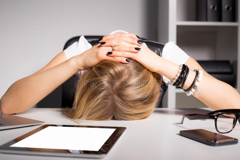 Zmęczona biznesowa kobieta odpoczywa jej głowę na biurku zdjęcia stock